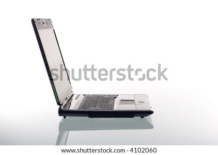 A modern laptop computer with reflection on a glass surface. Studio shot.