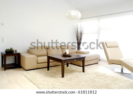 A modern living room with table, sofa and armchair.