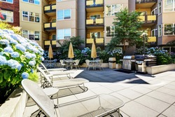 A modern loft courtyard with tables and chairs, barbecue area. New apartment house. Northwest, USA