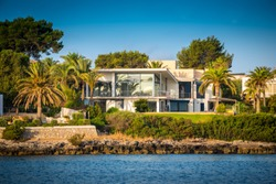 A modern luxurious seafront property located in Mallorca, Spain, with contemporary design, big glass windows. green garden with palm trees and the sea in front on a sunny day