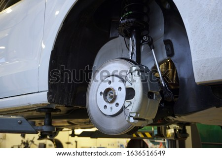 A modern luxury car at a service station is lifted on a lift for repair.  Front brake disc, caliper. Quality after-sales service concept.