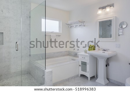 A modern, marble tile bathroom with an open walk-in shower and bathtub