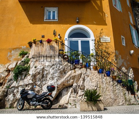 A modern motorcycle parked by an old stone staircase leading to an orange stucco villa