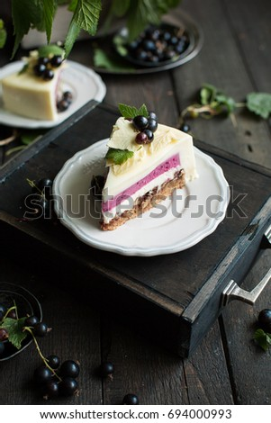 A modern mousse cake with a crusty nut layer, a layer of black wild currant and a mousse of white chocolate and yogurt. The cake is decorated with fresh currant berries and leaves of white chocolate