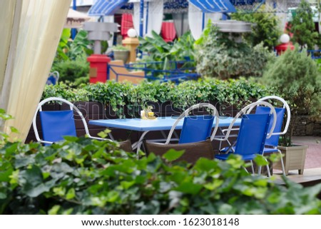 A modern outdoor cafe outdoors surrounded by beautiful greenery on a warm summer day without customers