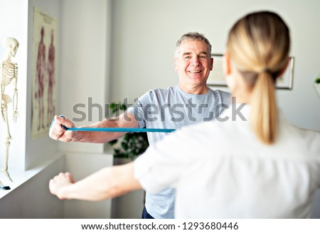 A Modern rehabilitation physiotherapy worker with senior client ストックフォト ©