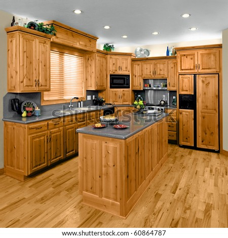 A modern residential kitchen, with hickory cabinets. - stock photo