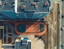 a modern school with a basketball court next to a multi-storey residential building. top view of the sports ground next to the gymnasium. school in eastern europe. 4k Aerial
