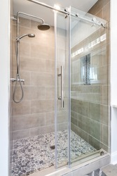 A modern shower with a stone floor, chrome fixtures, sliding glass door, and marble tiling on the walls.