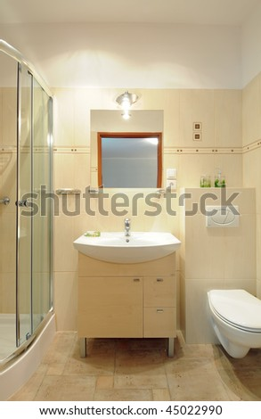 A modern sink on the wooden cupboard in a tiled bathroom underneath a mirror.