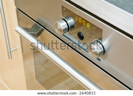 A modern stainless steel oven detail showing the knobs and door