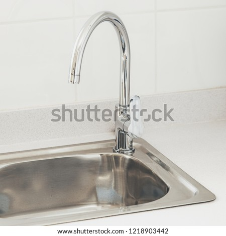 A modern stainless steel water faucet.  This image can also be used to represent the concept of water saving or washing.