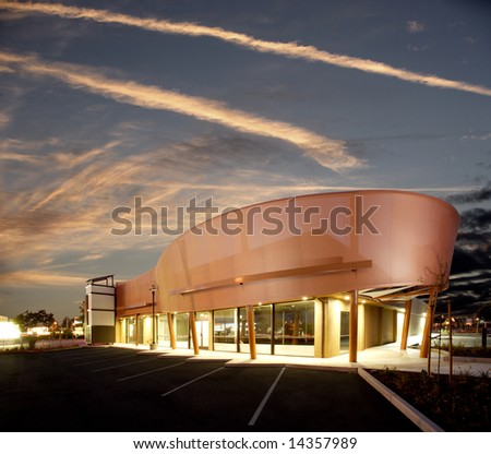 A modern strip mall with the sun setting