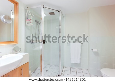 A modern style bathroom featuring a walk-in shower, a towel hanger and a wash basin with cabinet