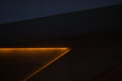 A modern wall with a yellow light line from a futuristic building at night with a nice pattern which can be used as background