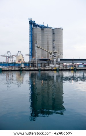 A modern waterfront commercial silo factory that allows freighters to load and unload material for production.