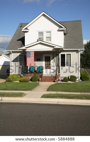 A modest house with an American flag, in a small town.