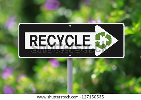 A modified one way sign on recycling (with a nature background) - stock photo