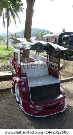 A modified scooter that is used to transport people as a taxi. Widespread on Sulawesi in the city of Kotamobag. Red motorbike. The original passenger transport vehicle. Rarity. #1442022680