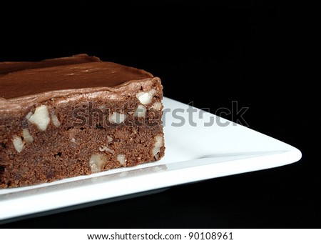 A moist, fudge chocolate brownie with nuts and chocolate icing on a square white plate on a black background. - stock photo
