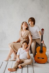 A mom and two sons in beige and white clothes pose for a photo shoot in the studio. happy single mother. memorabilia for the family. relationship between teenage children and parents. playing guitar