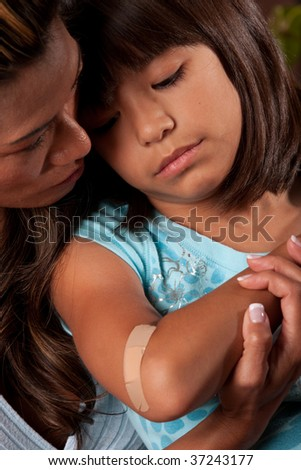 a mom comforts her young daughter who has a wound