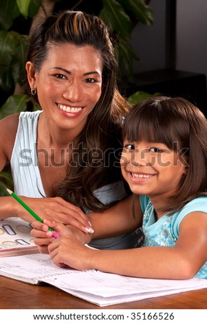 a mom helps her daughter with homework