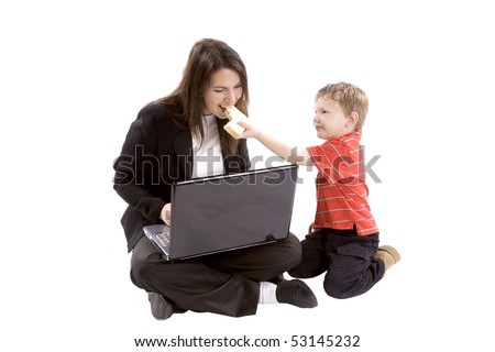 A mom is working on her computer while her son gives her a bite of his sandwich