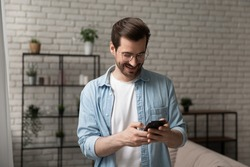 A moment to hear your voice. Hopeful young male stand at living room involved in dialing number of beloved female on cell. Loving boyfriend chatting with girlfriend in mobile phone app planning date