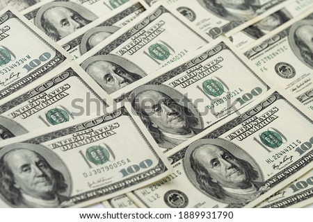 A money pile of one hundred US banknotes with president Franklin portrait. Cash of hundred dollar bills, paper currency background.