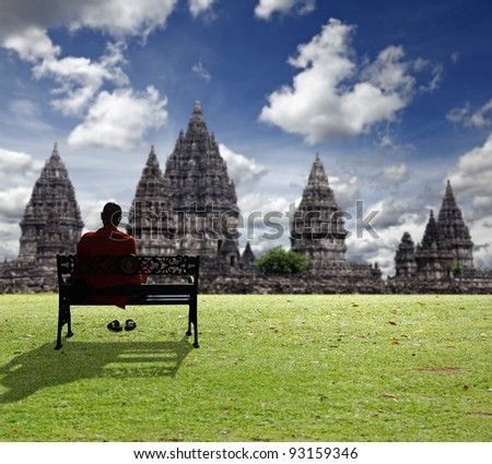 A monk meditating on a vintage ornamental bench on a grassy hill overlooking the ancient Prambanan hindu temple ruin on a blue cloudy day, in Jogjarkata, Indonesia.