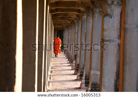 A monk walking through an ancient hall.