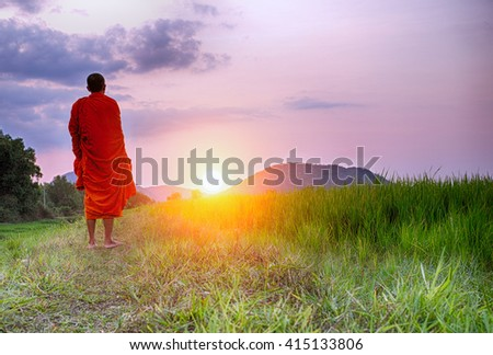 A Monk walks a path towards a setting sun in Cambodia or could be any South East Asian country. This monk's face is not shown and could be any monk.
