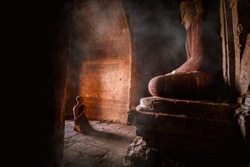 A Monks of Buddhism come make meditation and respect Ancient buddha statue at Dhammayangyi Temple a Buddhist temple located in Bagan, Myanmar,with sunlight ray background