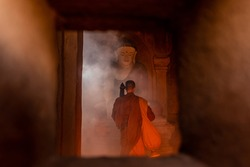 A Monks of Buddhism come to visit and respect Ancient buddha statue at Dhammayangyi Temple a Buddhist temple located in Bagan, Myanmar,with sunlight ray background