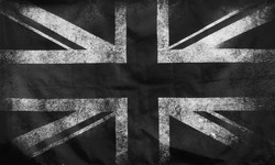 a monochrome full frame image of an old stained dirty union jack british flag with dark crumpled edges
