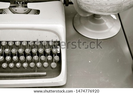 A monochrome image of a vintage typewriter and globe sitting on a desk, its keyboard awaiting the touch of a travel writer. #1474776920