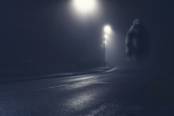 A monster with glowing eyes, floating above an empty road on a foggy winters night