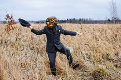 a monstrous Scarecrow with a Halloween pumpkin on his head dancing in a wild field dressed in a business suit