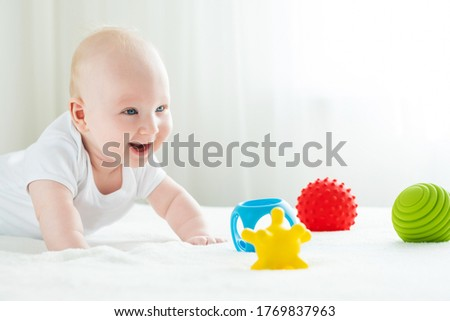 A 4 month old baby boy lies on his stomach with emphasis on his hands. He smiles and plays with colorful curly rubber toys. Foto stock ©