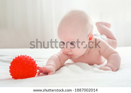 A 4 month old baby boy lies on his stomach with emphasis on his hands. He tries to reach for the red rubber ball. Motor development of the baby. Foto stock ©
