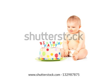 A 9 months old baby in diapers sitting next to a birthday cake isolated against white background