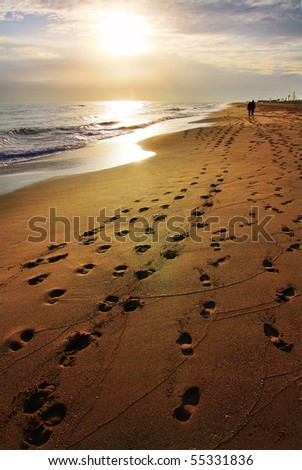 A moody, almost lonely beach - there are a lot of footprints on the sand and the sun is approaching the horizon line.