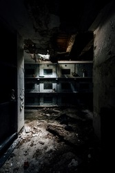 A moody, dark hallway leads to coffins and plaques inside a long abandoned mausoleum.