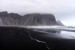 A moody, dark landscape with ocean waves crashing against a black sand beach with staggering mountains near Stokksnes, Iceland