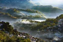 A morning city sunray valley landscape view of Aizawl city with clouds and rays in India