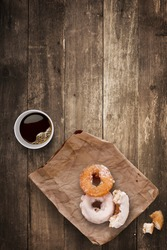 A morning lunch in the office consisted of a cup of black takeaway coffee and tasty donuts.