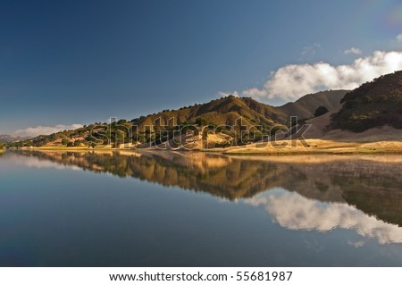 A morning reflection on Uvas Reservoir of the rolling hills and chaparral of the central California.