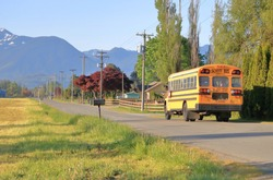 A morning rural school bus drives through a quiet country road in a beautiful agricultural valley.