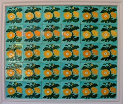 A mosaic of green tiles decorated with yellow flowers. These are typical of the tiles found on the facade of traditional Chinese Pernakan shop houses.